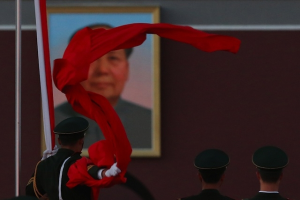 A paramilitary police officer collects the Chinese national flag during the flag-lowering ceremony at Tiananmen Square on November 13, 2012. (Feng Li/Getty Images)