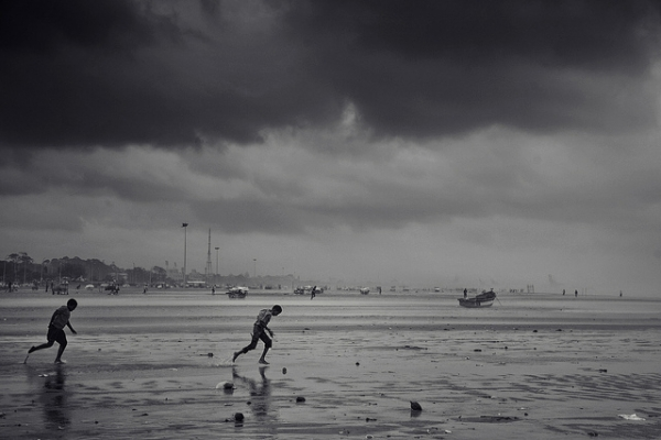As storm clouds gather, two boys run on the Marina Beach in Chennai, India on November 2, 2012. (VinothChandar/Flickr)