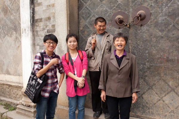 Four members of the installation team standing in front of Guanyu Tang, the ancestral hall in Pingshan Village built to honor Shu family ancestors dating to the Ming dynasty. L to R: Festival volunteers from Anhui University, Jiang Caijie and Qian Jinyue, and Pingshan locals, Mr. Shu and Ms. Shu. (Leah Thompson)