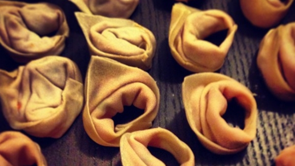 Folded dumplings filled with sweet potatoes, waiting to be deep-fried. (Tahiat Mahboob)