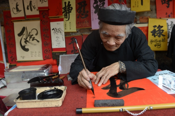 A calligrapher writes down best wishes for the lunar new year or Tet in Vietnamese, for customers outside the Temple of Literature in downtown Hanoi, Vietnam on February 8, 2013. (Hoang Dinh Nam/AFP/Getty Images)