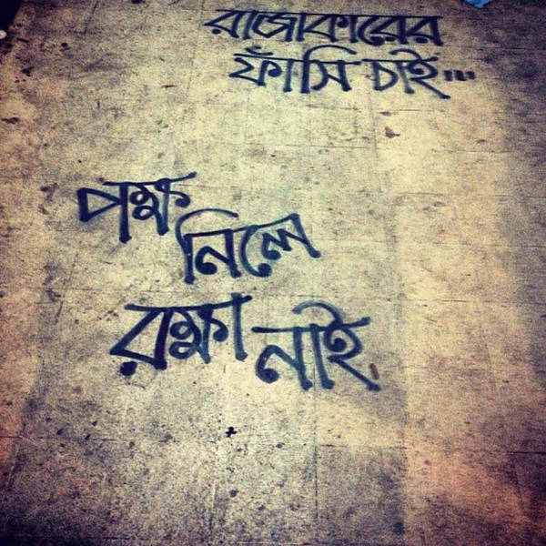"Bangla graffiti on the pavement reads: Hang the ""rajakar."" No protection for those who pick sides. (Naorose Bin Ali)"