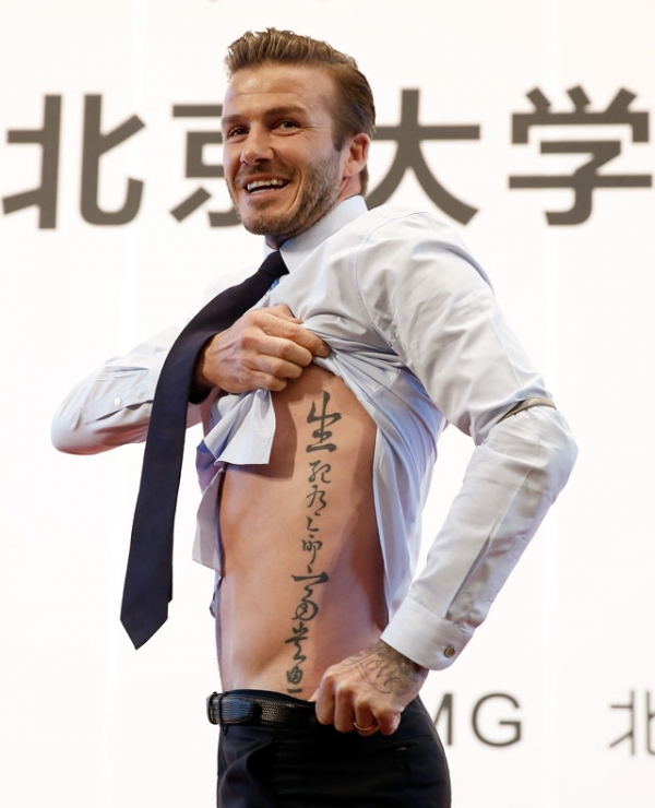 British football player David Beckham shows his tattoo to fans during his visit to Peking University on March 24, 2013 in Beijing, China. (Lintao Zhang/Getty Images)