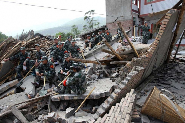 Rescuers sit on ruins of a house in Longmen township, close to the epicenter of a magnitude 7.0 earthquake that hit the city of Ya'an, southwest China's Sichuan province on April 20, 2013. (STR/AFP/Getty Images)
