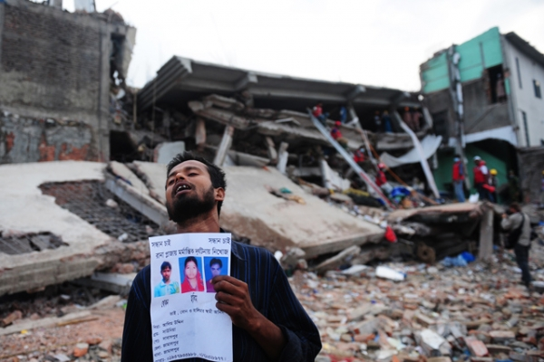 A Bangladeshi man holds a portrait of his missing relatives, believed trapped in the rubble of an eight-storey building that collapsed in Savar, on the outskirts of Dhaka, Bangladesh on April 28, 2013. (Munir Uz Zaman/AFP/Getty Images)