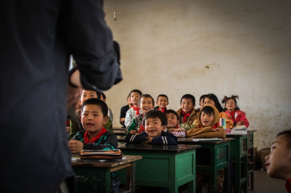 A classroom full of children smile and listen attentively to their teacher in Jizushan, Yunnan Province, China on March 6, 2013. (James Moallem)