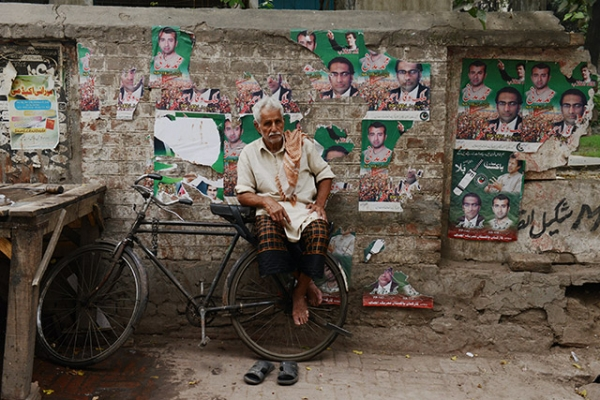 An ice vendor sits on his bicycle in front of a wall covered with political posters in Lahore, Pakistan on May 10, 2013. (Roberto Schmidt/AFP/Getty Images)