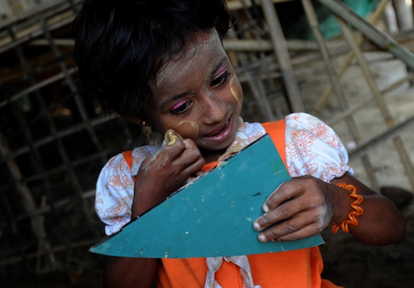 A child of the Rohingya minority group applies a traditional cosmetic paste at an IDP camp in Sittwe, Myanmar on May 18, 2013. (Soe Than Win/AFP/Getty Images)