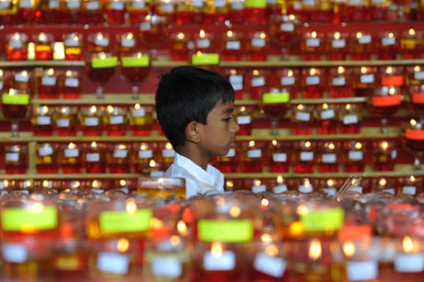 A young Buddhist devotee walks past rows of candles for Vesak Day celebrations at a Buddhist temple in Kuala Lumpur, Malaysia on May 24, 2013. (Mohd Rafsan/AFP/Getty Images)
