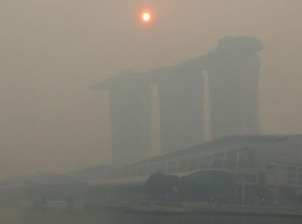 The mid-morning sun struggles to shine through a thick smoke haze above the three towers of the Marina Bay Sands casino resort on Singapore, Friday June 21, 2013. (Geoff Spencer)