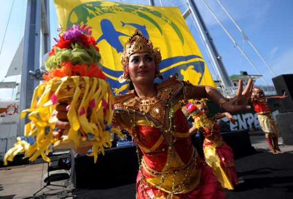 Dancers clad in vibrant colors perform during a welcoming ceremony to greet Greenpeace's Rainbow Warrior ship in Bali, Indonesia on May 31, 2013. (Sonny Tumbelaka/AFP/Getty Images)