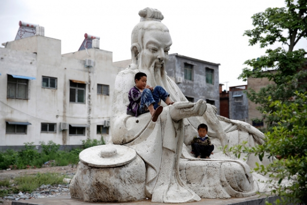 Two children play on a statue outside a factory in Shifosi town, the biggest jade center in the world in Henan, China on May 31, 2013. (Lintao Zhang/Getty Images)