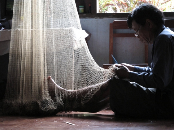 A village chief mends his fishing net in Ban Pong Song, Laos on June 5, 2013. (Steel Wool/Flickr)