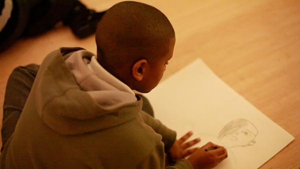A visiting student sits inside the Asia Society Museum and draws at the Lin Tianmiao exhibit. (Tahiat Mahboob/Asia Society)