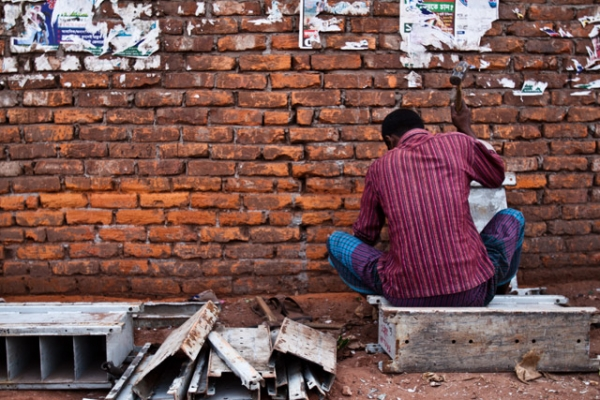 Man breaks down sections of scrap steel with a hammer by the Buriganga river in Dhaka, Bangladesh on January 27, 2013. (Rob Pinney)
