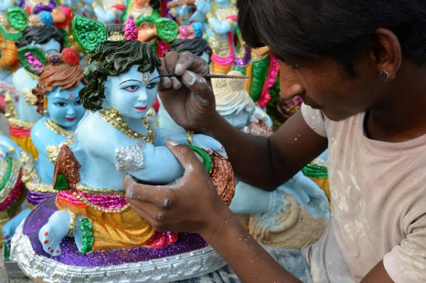 Indian artist Suresh paints an idol of the Hindu Lord Krishna at a roadside stall on the outskirts of Amritsar on August 25, 2013. (Narinder Nanu/AFP/Getty Images)