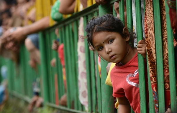 A child leans out from behind a barrier to watch a competition on the outskirts of Kathmandu, Nepal on August 23, 2013. (Prakash Mathema/AFP/Getty Images)