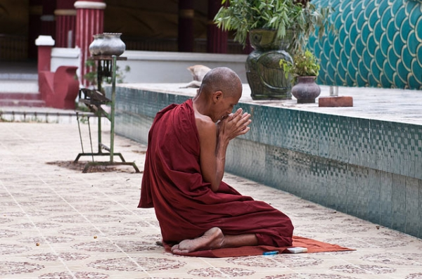 A monk pauses for a moment of prayer in Myanmar on September 7, 2013. (East.Lucky/Flickr)