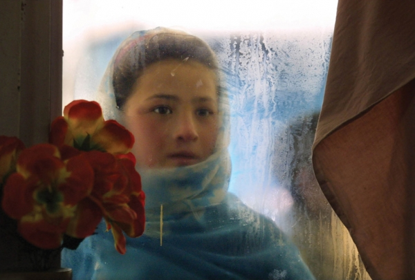 Kabul, 2002: Switan, age ten, looks into the window of the Herat restaurant. She gazes at people eating with the hopes of getting leftovers and makes 50,000 to 70,000 Afghani ($2.50 U.S.) per day begging from foreigners. (Paula Bronstein/Getty Images)