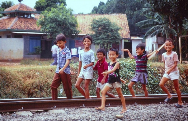 Children amuse themselves as they play along a railroad in West Java, Indonesia on September 11, 2013. (Kent Clark/Flickr)