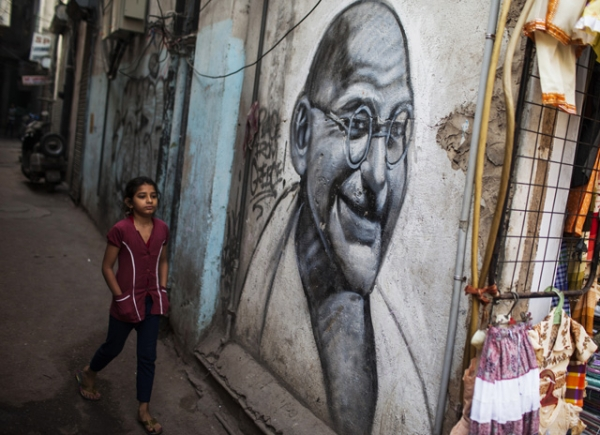 A girl walks past a painting of Mahatma Gandhi in an alleyway in New Delhi, India on March 17, 2013. (Andrew Caballero-Reynolds/AFP/Getty Images)