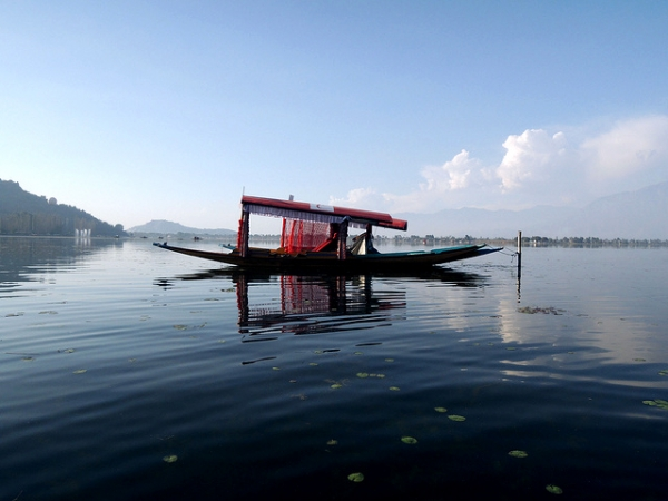 "A red boat, also called a ""shikara"" is anchored in calm waters at Dal Lake, Kashmir on November 1, 2013. (BOMBMAN/ Flickr)"