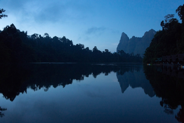 Houses, trees and mountains cast shadows on still waters in Khao Sok, Thailand on November 3, 2013. (Stefan Magdalinski/Flickr)