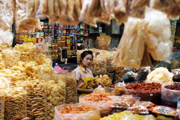A shopkeeper is surrounded by her dried goods and wares at an indoor market in Bangkok, Thailand on January 1, 2014. (Tord Sollie/ Flickr)