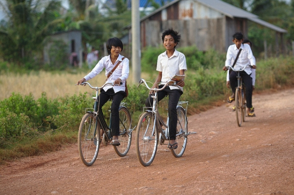 Students gleefully bike down a dirt road as they bike home from school on Fish Island, Cambodia on January 14, 2014. (Maciej Hrynczyszyn/ Flickr)