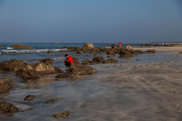 Tourists search for shells on the untouched Ngwe Saung Beach in Yangon, Burma on January 26, 2014. (Lauren DeCicca/Getty Images)