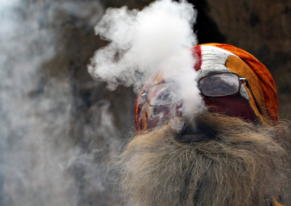 A Hindu Sadhu smokes from a clay pipe as a holy offering for Lord Shiva during Maha Shivaratri in Kathmandu, Nepal on March 2, 2011. (Prakash Mathema/AFP/Getty Images)