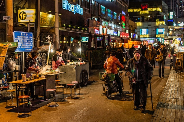 An old man walks along a bustling street at night in Beijing, China on January 12, 2014. (Zhou/Ding/Flickr)