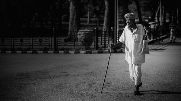 An old man goes out walking with a stick on the streets of Bangalore, India on March 29, 2014. (Soumya Geetha/Flickr)