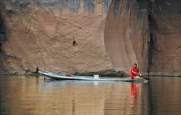 Dressed in bright red, a boatman paddles his way through calm waters in Laos on March 19, 2014. (jean jacques chaffois/Flickr)