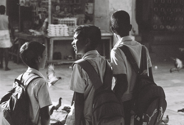 Three school boys walk and talk on a street in Nagore, India on May 1, 2014. (Nagoor Dargah/Flickr)