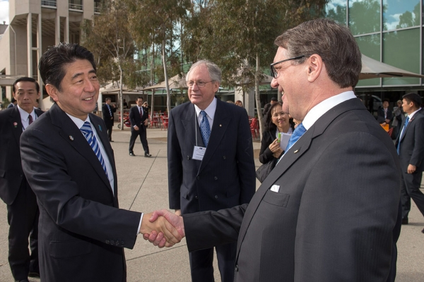 Shinzo Abe (L), Prime Minister of Japan, greets Warwick Smith (R), Chairman of Asia Society Australia, as Sir Rod Eddington, President Australia Japan Business Co-operation Committee, looks on in this photos taken July 8, 2014, in Canberra. (Irene Dowdy)