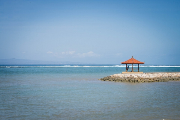 A man stands under a gazebo overlooking the ocean at Sanur Beach in Bali, Indonesia on September 11, 2014. (Darien Graham-Smith/Flickr)