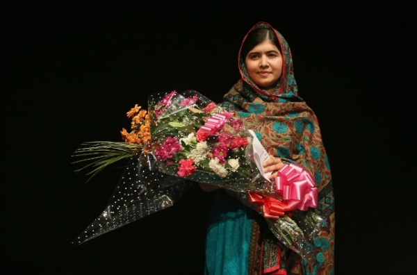 After being announced as a recipient of the Nobel Peace Prize, Malala Yousafzai holds a bouquet of flowers given to her on behalf of the Pakistani Prime Minster during a press conference at the Library of Birmingham in Birmingham, England, on Oct. 10, 2014. (Christopher Furlong/Getty Images)