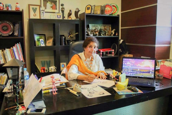 "Shown here in her Islamabad office, Nigar Nazar is Pakistan's first professional female cartoonist, known to generations of readers as the creator of the iconic character ""Gogi."" (Gogi Studios)"