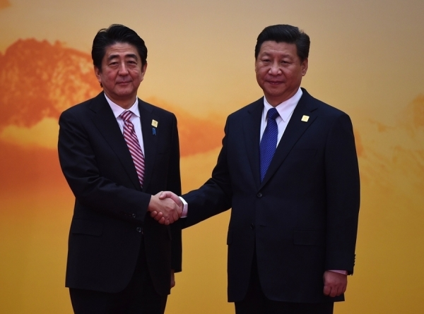Japan's Prime Minister Shinzo Abe (L) shakes hands with China's President Xi Jinping as he arrives for the Asia-Pacific Economic Cooperation (APEC) leaders meeting at Yanqi Lake, north of Beijing on November 11, 2014. (Greg Baker/Getty Images)