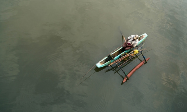 A lone fisherman rows on calm green waters to go catch fish in Sri Lanka on October 4, 2014. (Kolitha de Silva/Flickr)