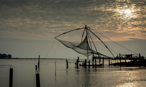 A man rows his boat beneath an empty fishing net hung in the air from some poles in Kerala, India on December 5, 2014. (L0bit0/Flickr)