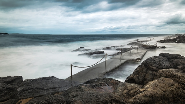 Misty waves crash over rocks in New South Wales, Australia on December 10, 2014. (Glen R90/Flickr)