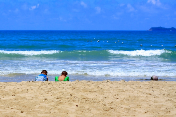 Two little Chinese boys play with beach sand in Sanya, Hainan Province, China on June 1, 2014. (Hai yizhe/Flickr)