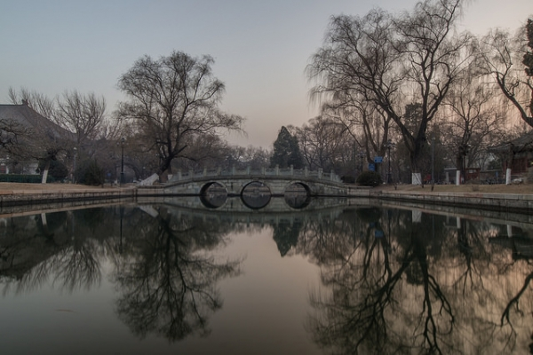 A bridge flanked by trees forms a serene reflection in a pond in Beijing, China on January 8, 2015. (Jens Schott Knudsen/Flickr)