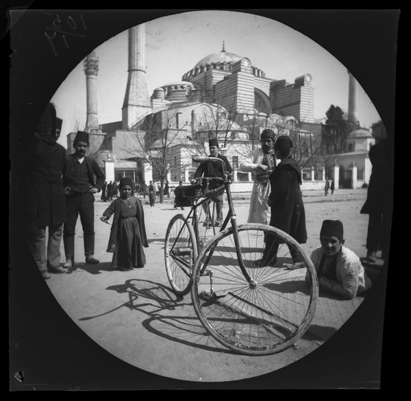William Sachtleben's Humber bicycle at rest in Constantinople draws a crowd of spectators.  Background: Hagia Sophia and Thomas Allen on his bicycle, March 21, 1891, Collection of the UCLA Library Special Collections