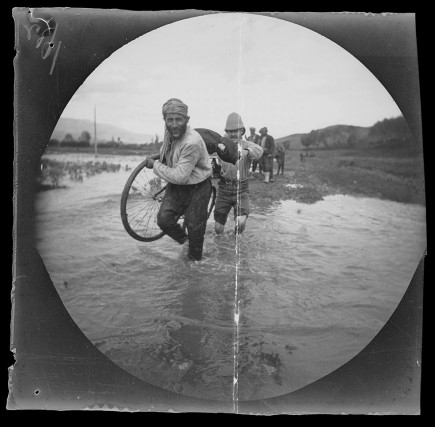 A hired guard helps William Sachtleben carry his bicycle and gear across a stream in Turkey, May 26, 1891, Collection of the UCLA Library Special Collections