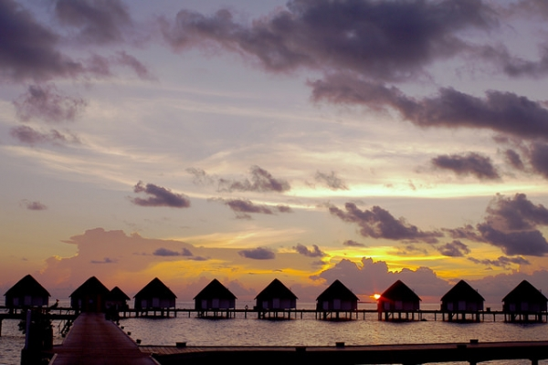 A row of houses stand silhouetted against the setting sun in Centara Grand Island, Maldives on May 1, 2015.(michibanban/Flickr)