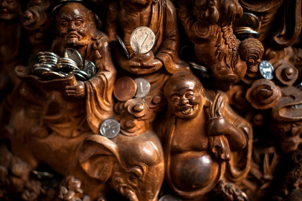 Intricately carved figures of Buddha and other religious figures are laden with offerings at the Jade Buddha Temple in Shanghai, China on March 29, 2015. (Tybo/Flickr)