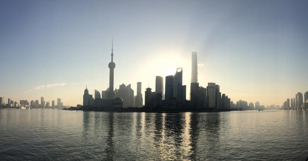 The sun peeks through tall buildings clustered around the water in Shanghai, China on October 3, 2015. (機智的阿卡林醬/ Flickr)
